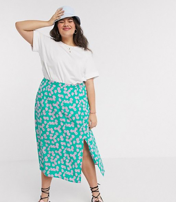 A plus-size model wearing a green printed midi skirt.