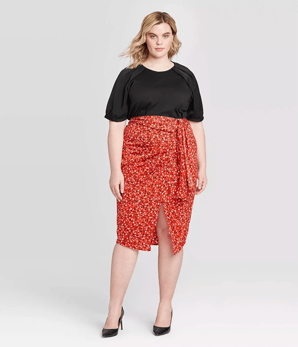 A plus-size model wearing a red printed midi skirt.