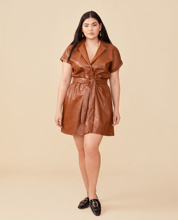 A plus-size model wearing a brown leather mini dress.
