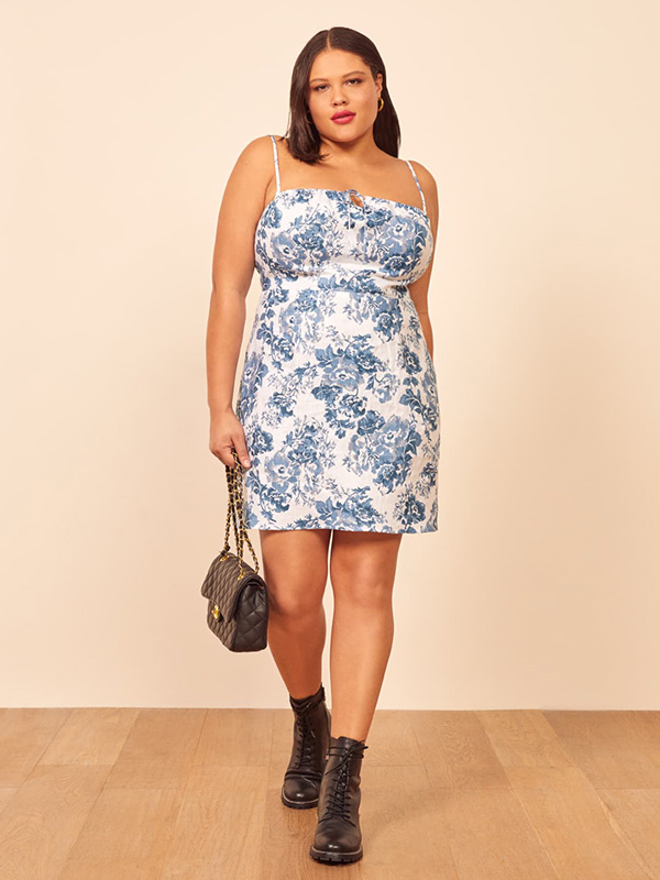 A plus-size model wearing a blue printed mini dress.