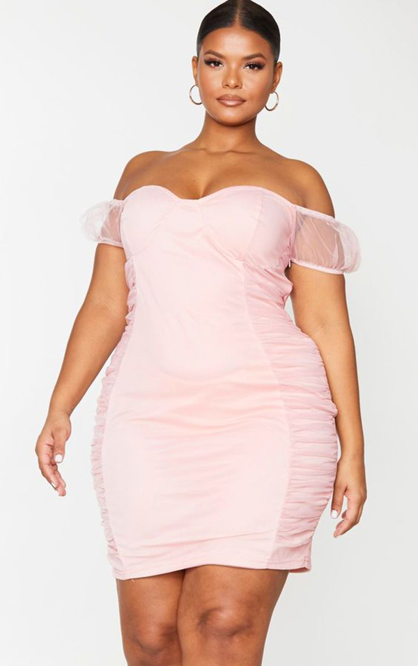 A plus-size model wearing a light pink ruched mini dress.