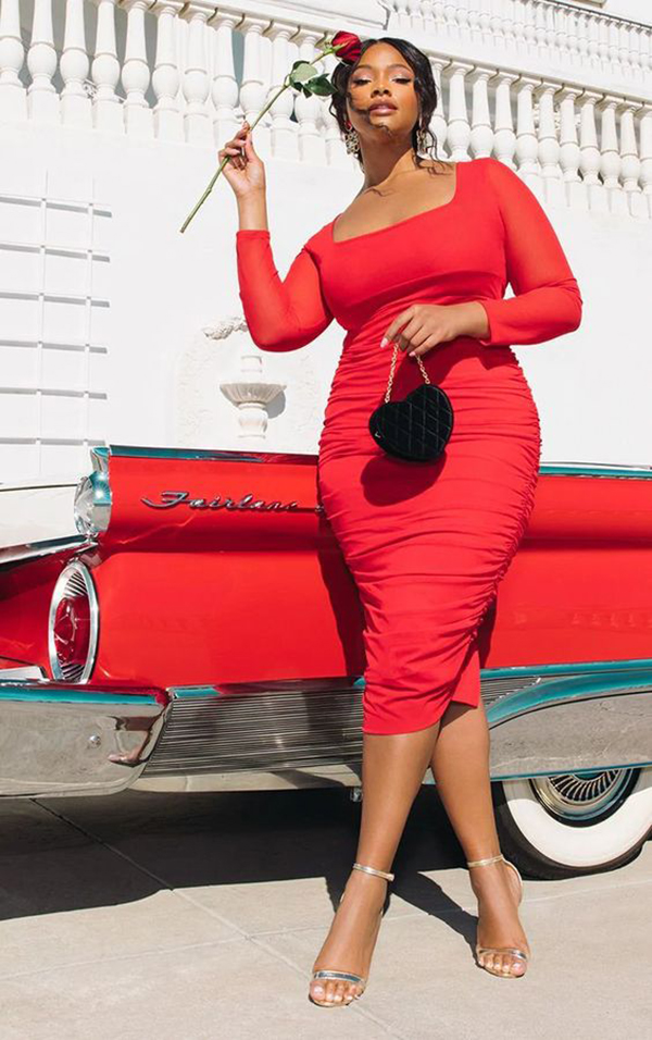 A plus-size model wearing a red ruched midi dress.