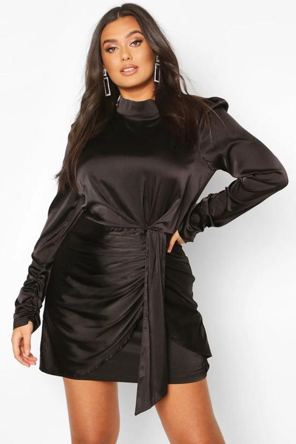 A plus-size model wearing a black ruched mini dress.