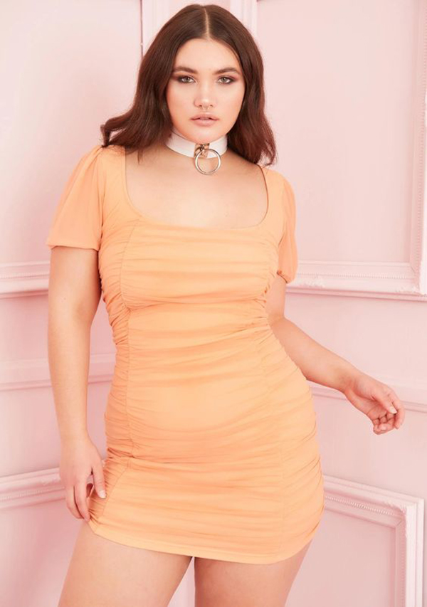 A plus-size model wearing an orange ruched dress.