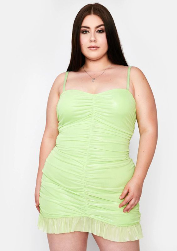 A plus-size model wearing a lime green ruched mini dress.