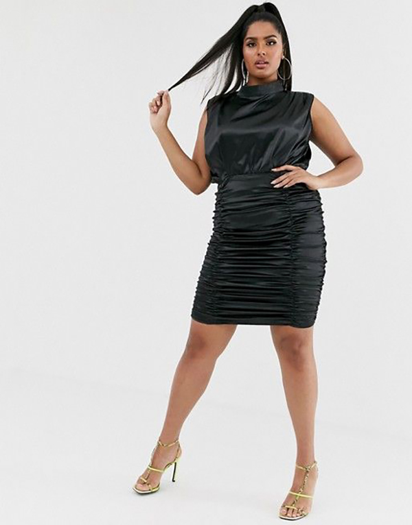 A plus-size model wearing a black ruched dress.