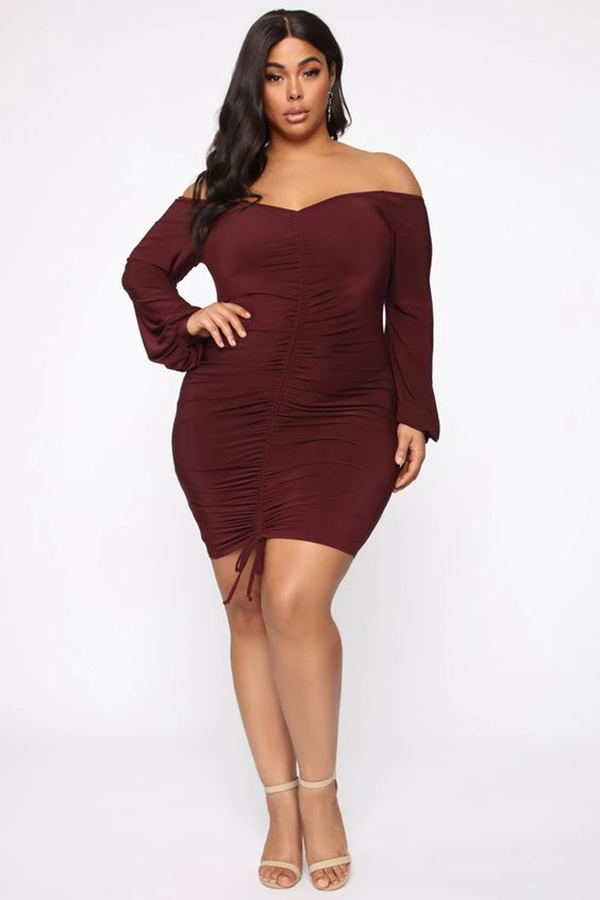 A plus-size model wearing a burgundy ruched mini dress.