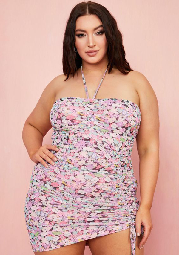 A plus-size model wearing a floral ruched mini dress.
