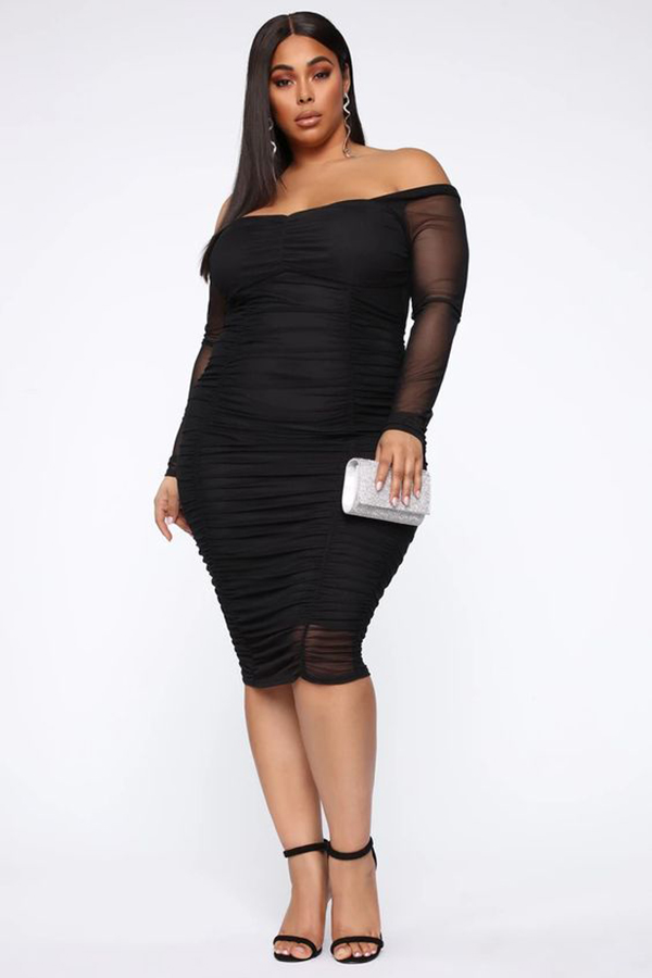 A plus-size model wearing a black ruched midi dress.
