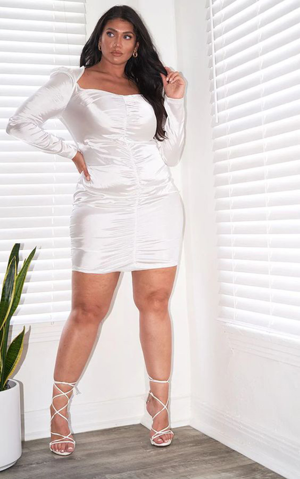 A plus-size model wearing a white ruched mini dress.