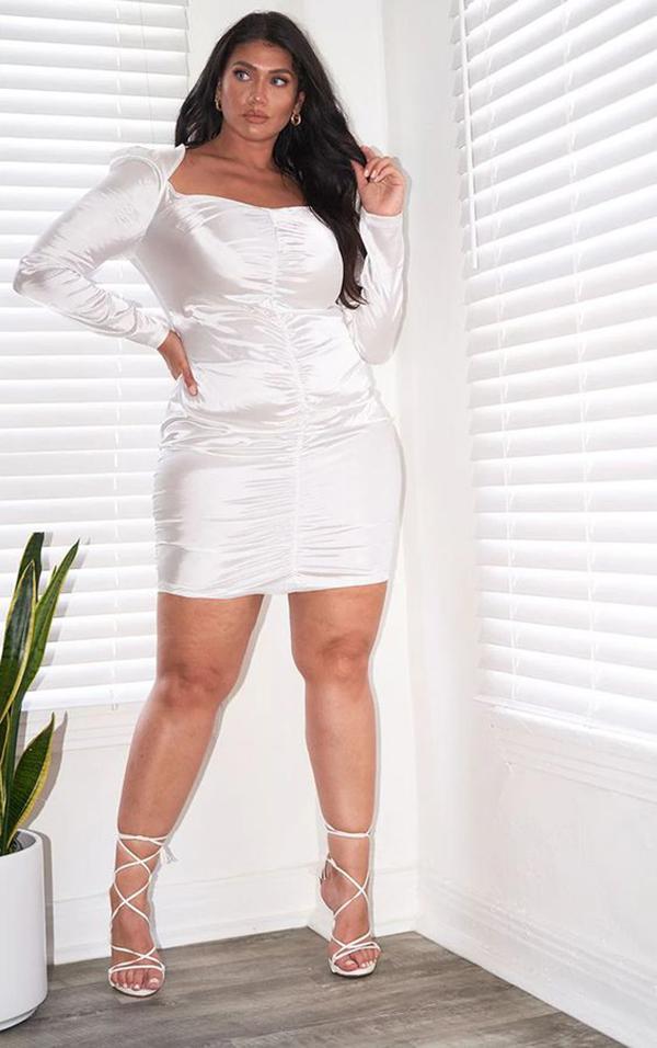 A plus-size model wearing a white ruched mini dress.