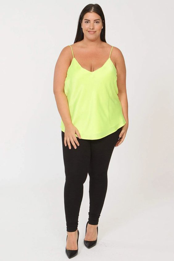 A plus-size model wearing a neon yellow satin cami.