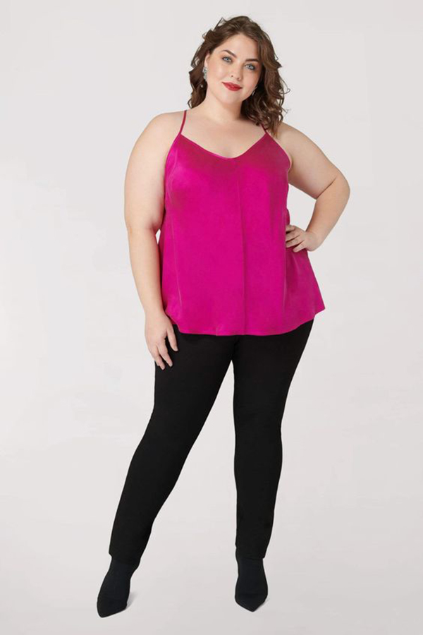 A plus-size model wearing a hot pink satin cami.