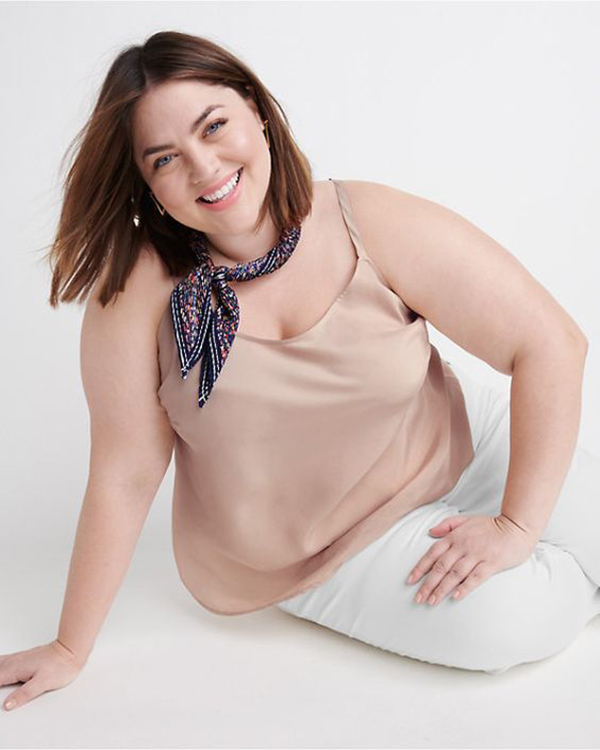 A plus-size model wearing a champagne satin cami.