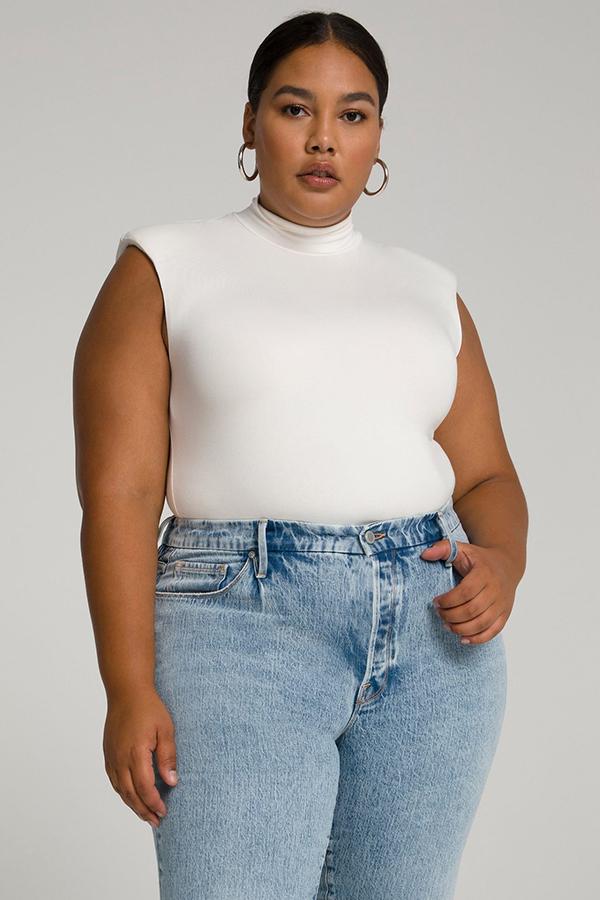 A plus-size model wearing a white shoulder pad turtleneck bodysuit.