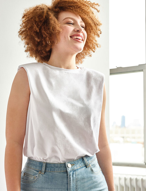 A plus-size model wearing a white shoulder pad tee.