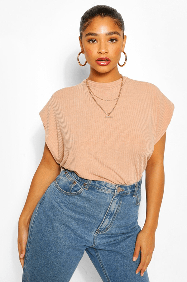 A plus-size model wearing a camel colored shoulder pad tee.