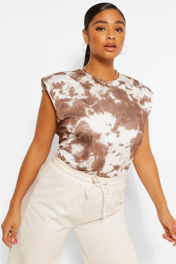 A plus-size model wearing a brown tie-dye shoulder pad tee.