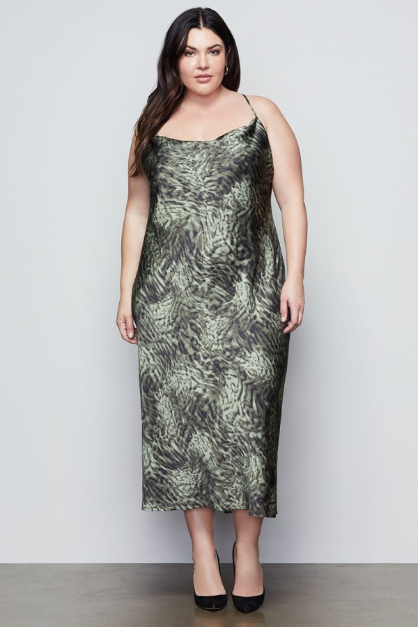 A plus-size model wearing a green printed slip dress.