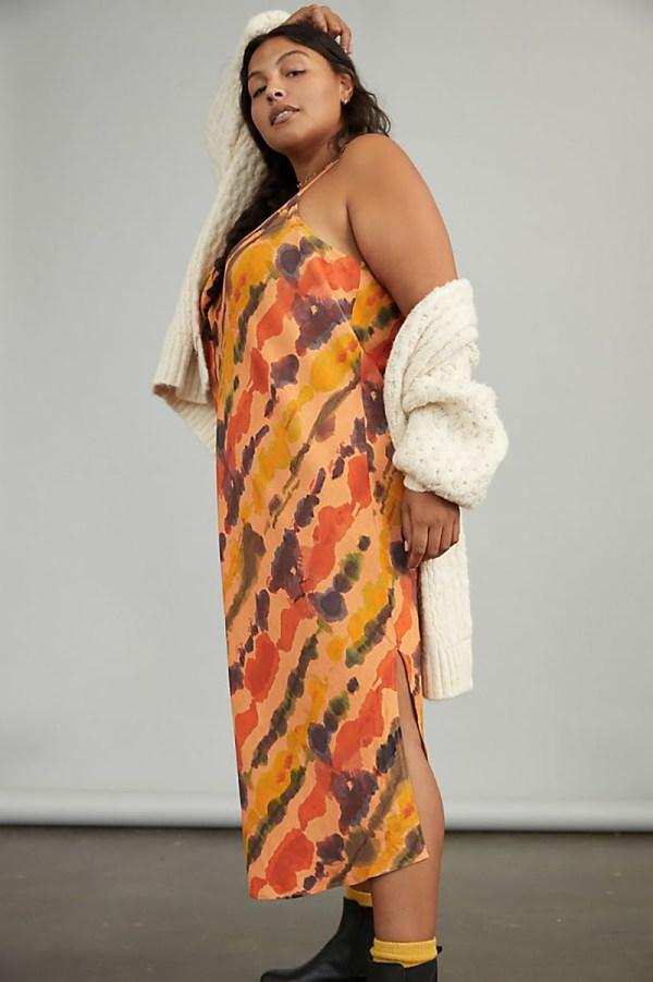 A plus-size model wearing an orange tie-dye slip dress.