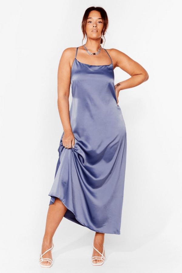 A plus-size model wearing a periwinkle maxi slip dress.