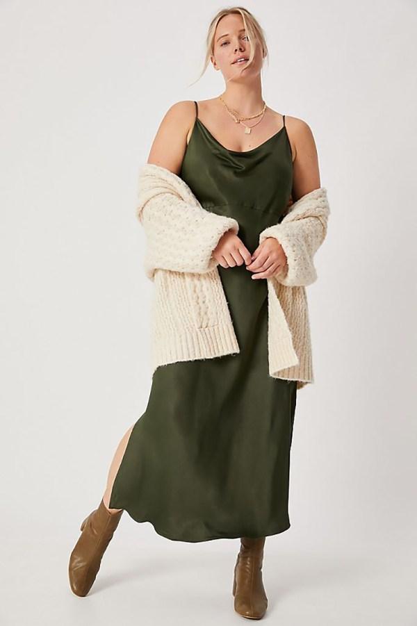 A plus-size model wearing an olive green slip dress.