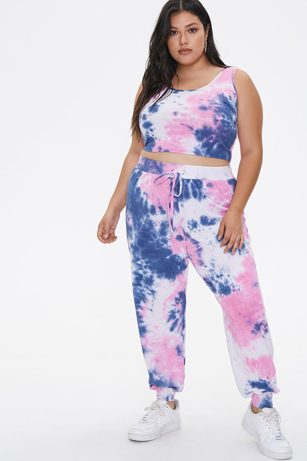 A plus-size model wearing a pink and purple tie-dye lounge set.