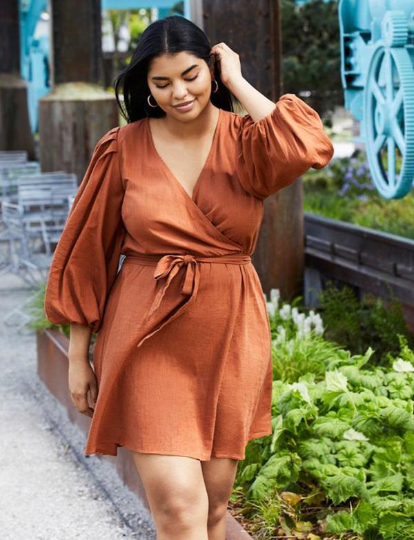 A plus-side model wearing a burnt orange wrap dress.