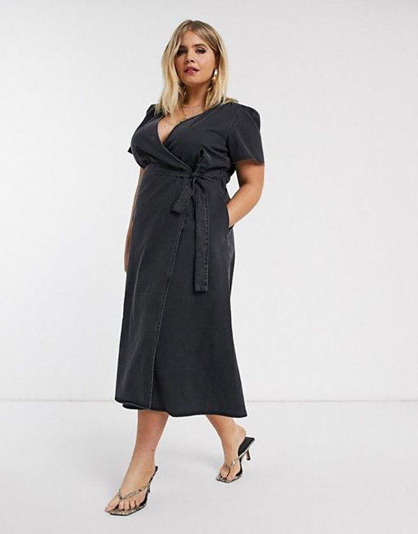 A plus-side model wearing a black denim wrap dress.