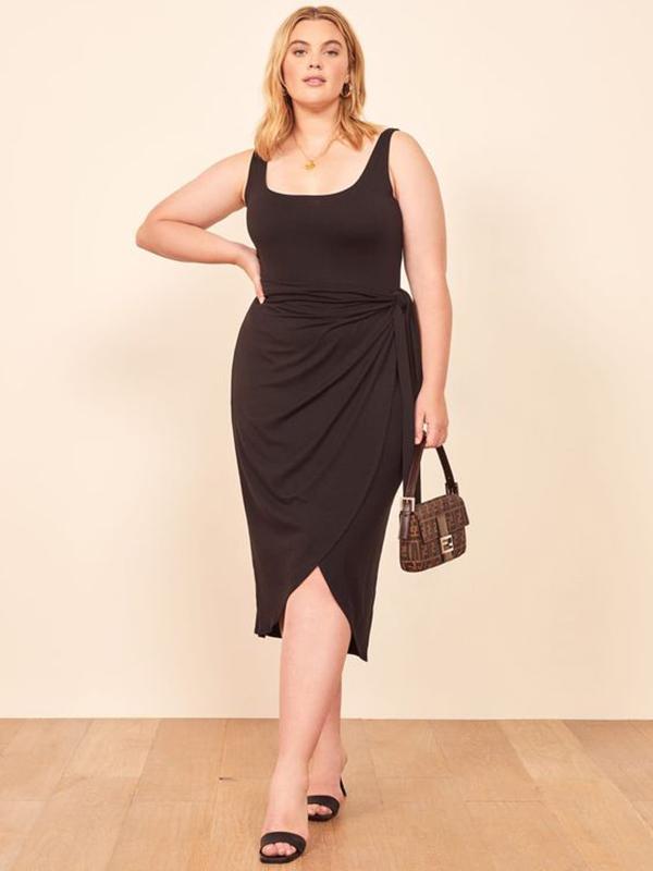 A plus-side model wearing a black, form-fitting wrap dress.