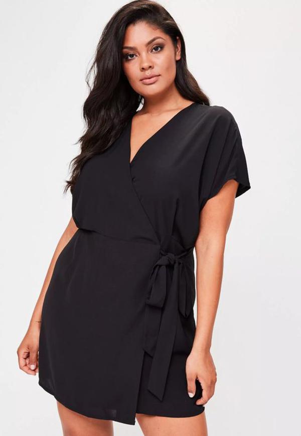 A plus-side model wearing a black wrap mini dress.
