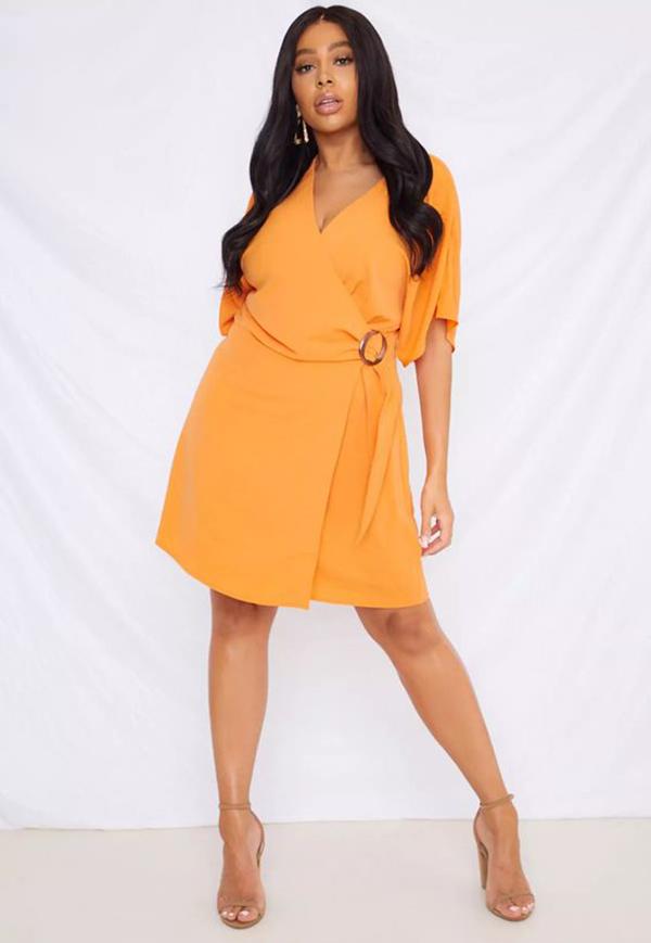 A plus-side model wearing an orange wrap dress.