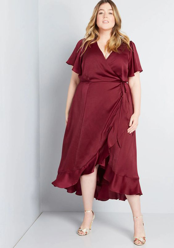 A plus-side model wearing a burgundy satin wrap dress.