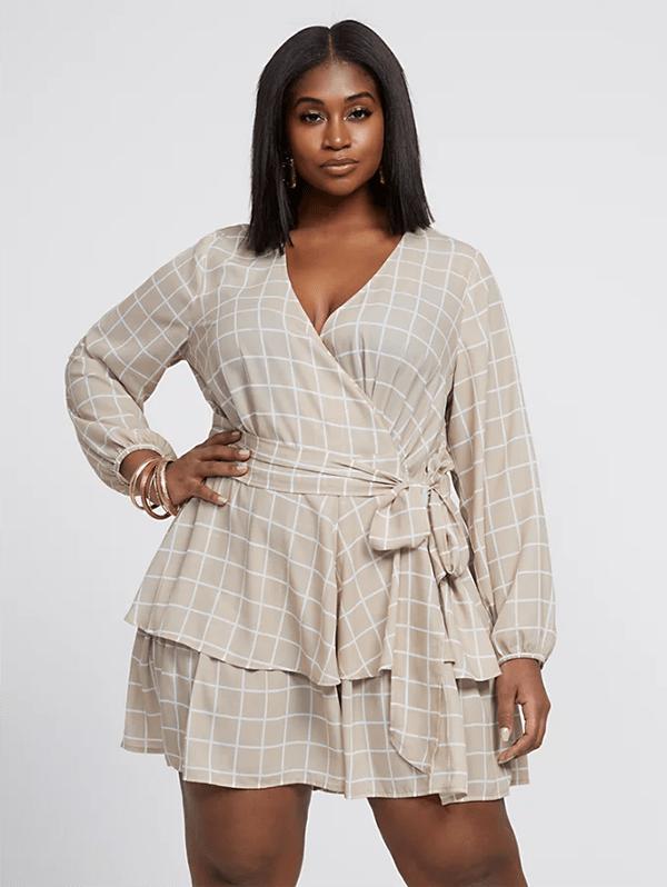 A plus-side model wearing a printed wrap mini dress.