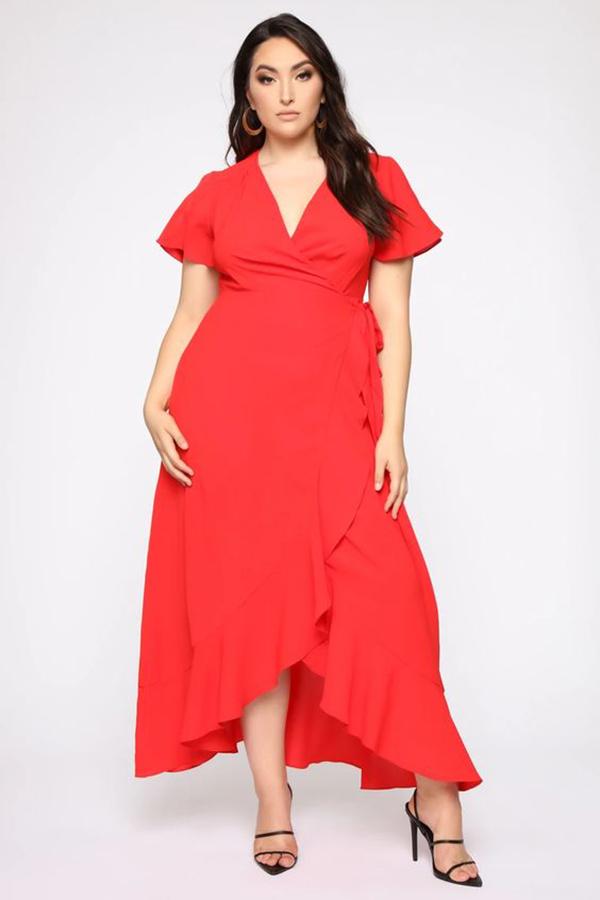 A plus-side model wearing a red wrap dress.