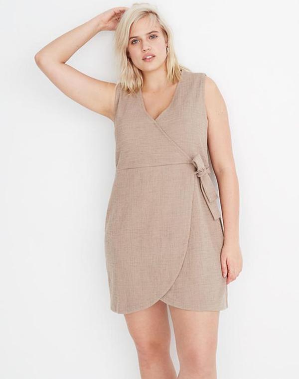 A plus-side model wearing a khaki wrap mini dress.