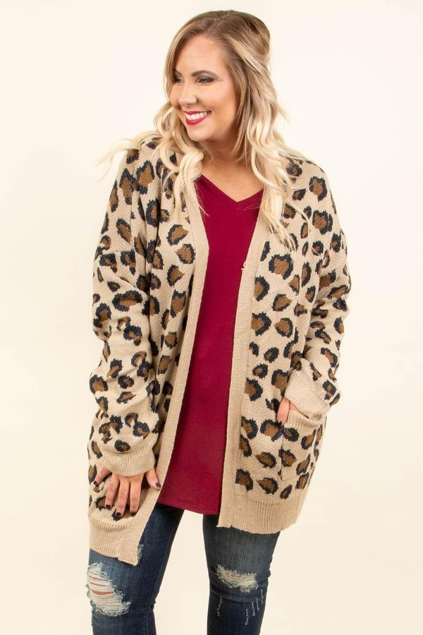 A plus-size model wearing a leopard print cardigan.