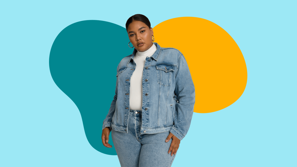 A plus-size model wearing a denim jacket and white turtleneck.