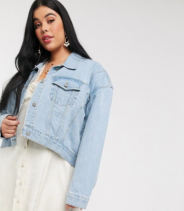 A plus-size model wearing a cropped denim jacket.