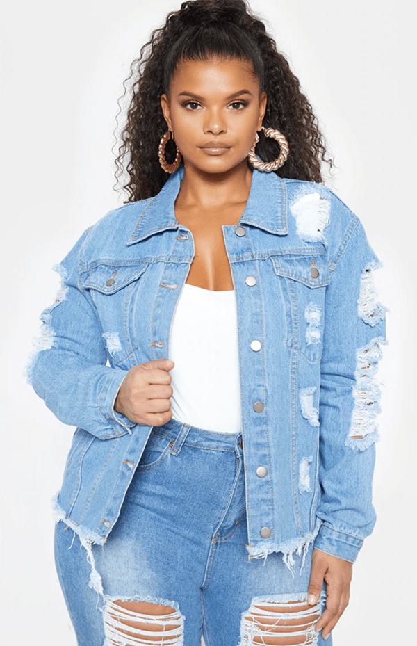 A plus-size model wearing a distressed denim jacket.