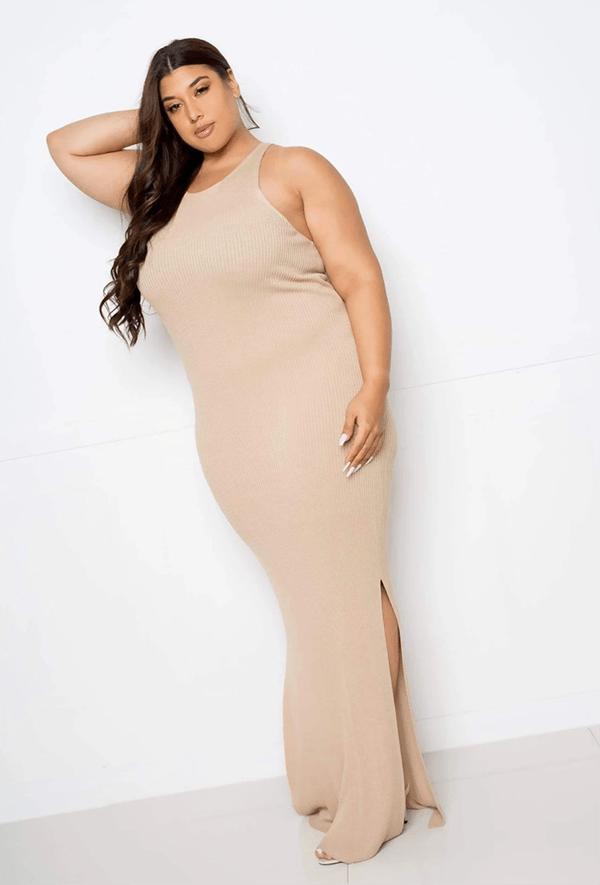 A plus-size model wearing a beige, form-fitting fall maxi dress.