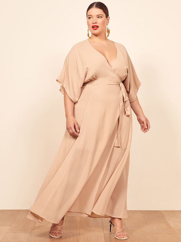 A plus-size model wearing a beige fall maxi dress.