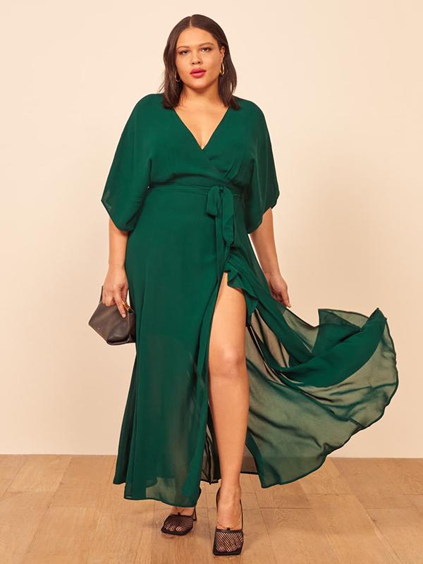 A plus-size model wearing an emerald green fall maxi dress.