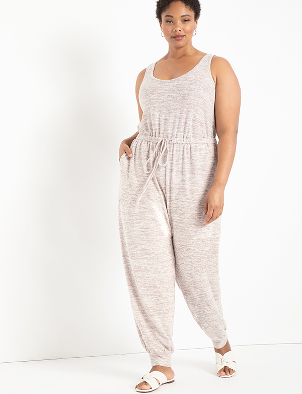 A plus-size model wearing a beige lounge jumpsuit.