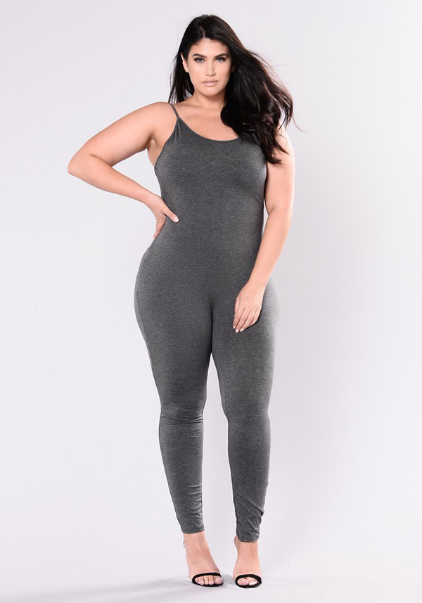 A plus-size model wearing a charcoal gray lounge jumpsuit.