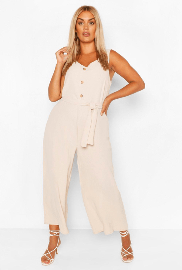 A plus-size model wearing a white lounge jumpsuit.