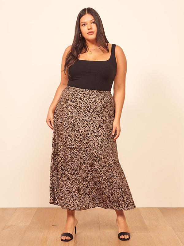 A plus-size model wearing a cheetah print maxi skirt.