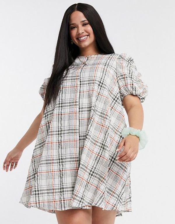 A plus-size model wearing a plaid mini dress.