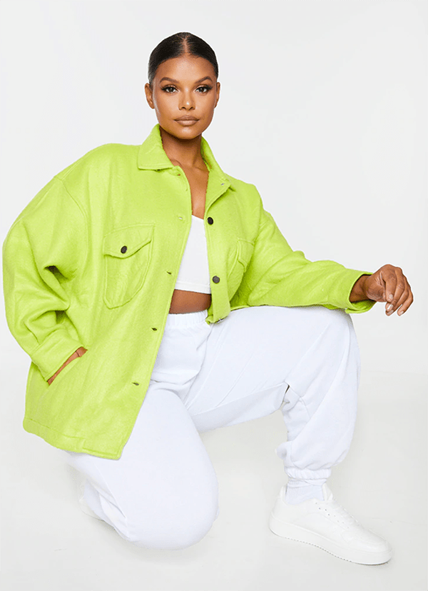 A plus-size model wearing a lime green shacket.