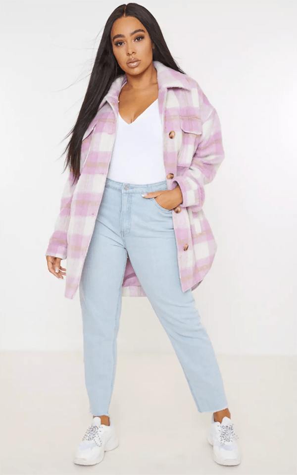 A plus-size model wearing a pink plaid shacket.